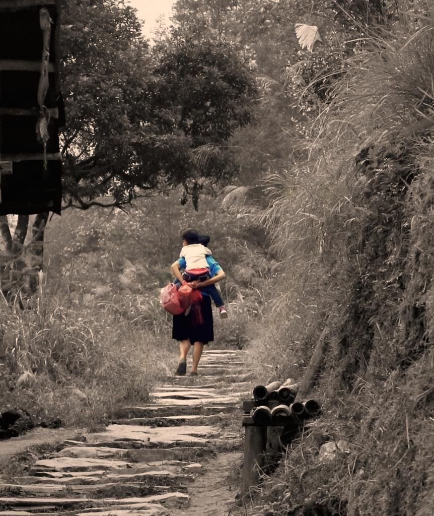 Seorang ibu menjemput anaknya dari sekolah dan menggendong nya naik turun bukit untuk sampai di rumah